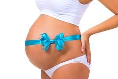 Nahaufnahme des schwangeren Bauches mit blauem Band und Bogen Konzept der Schwangerschaft Neugeborenes Baby Stockbilder