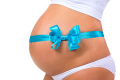 Nahaufnahme des schwangeren Bauches mit blauem Band und Bogen Konzept der Schwangerschaft Neugeborenes Baby Stockfotografie
