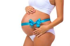 Nahaufnahme des schwangeren Bauches mit blauem Band und Bogen Konzept der Schwangerschaft Neugeborenes Baby Stockfotos