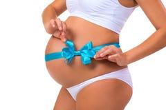 Nahaufnahme des schwangeren Bauches mit Bogen des blauen Bandes für neugeborenes Baby Konzept der Schwangerschaft Stockbild