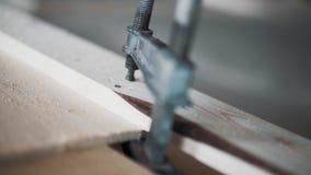Nahaufnahme des schwarzen metallischen Werkzeugs angeschlossen, um hölzerne Planke im Workhouse gelb zu färben stock video