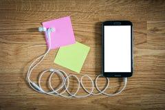 Nahaufnahme des schwarzen Smartphone mit weißem Schirm mit Kopfhörern, s Lizenzfreie Stockbilder