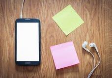 Nahaufnahme des schwarzen Smartphone mit weißem Schirm mit Kopfhörern, s Stockbild