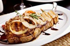 Nahaufnahme des Schweinefleischsteaks mit Zwiebel, Tomaten und Rosmarin Stockfotos