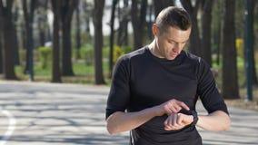 Nahaufnahme des Sitzrüttlers stoppend vom Laufen in den Park, der smartwatch Eignungsverfolger überprüft stock video