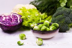 Nahaufnahme des sortierten Frischgemüses auf einem schwarzen Schiefer auf einem Holztisch: Kohl, Brokkoli, Blumenkohl und Brüssel Stockbilder