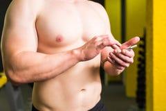 Nahaufnahme des sportiven Mannes nach Trainings-Sitzung überprüft Eignungs-Ergebnisse Smartphone Erwachsener Guy Wearing Sport Tr Lizenzfreie Stockbilder