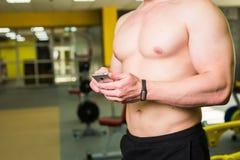 Nahaufnahme des sportiven Mannes nach Trainings-Sitzung überprüft Eignungs-Ergebnisse Smartphone Erwachsener Guy Wearing Sport Tr Stockbilder