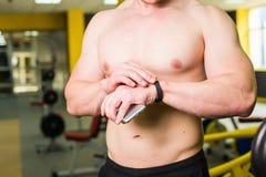 Nahaufnahme des sportiven Mannes nach Trainings-Sitzung überprüft Eignungs-Ergebnisse Smartphone Erwachsener Guy Wearing Sport Tr Stockfotos