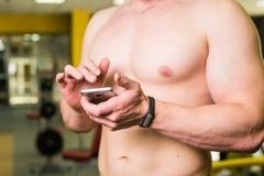 Nahaufnahme des sportiven Mannes nach Trainings-Sitzung überprüft Eignungs-Ergebnisse Smartphone Sport-Verfolger-Manschetten-Arm  Stockbild