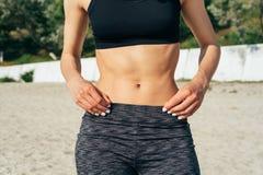 Nahaufnahme des sportlichen Mädchens mit einem flachen Bauch auf dem Strand Lizenzfreies Stockbild