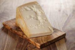 Nahaufnahme des Stückes italienischen Parmesankäseparmesankäses auf hölzernem Schneidebrett Stockfotografie