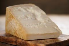 Nahaufnahme des Stückes italienischen Parmesankäseparmesankäses auf hölzernem Schneidebrett Stockbilder