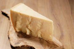 Nahaufnahme des Stückes italienischen Parmesankäseparmesankäses auf hölzernem Schneidebrett Lizenzfreies Stockbild