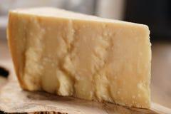 Nahaufnahme des Stückes italienischen Parmesankäseparmesankäses auf hölzernem Schneidebrett Stockfotos
