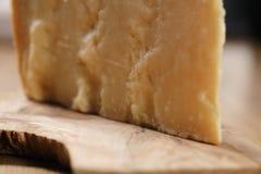 Nahaufnahme des Stückes italienischen Parmesankäseparmesankäses auf hölzernem Schneidebrett Stockbild