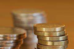 Nahaufnahme des Stapels der Münzen, goldener Hintergrund Lizenzfreie Stockbilder