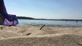 Nahaufnahme des Strandes und des Sandes mit Wasser und Wellen im Hintergrund an einem heißen Tag an Wannsee-Bad im Sommer stock video footage