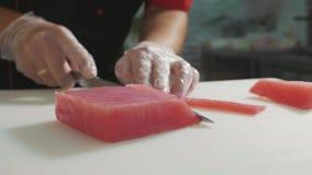 Nahaufnahme des Sushichefs in den Handschuhen schneidet frisches rotes Fischfilet am Sushi-Bar stock video footage