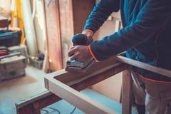 Nahaufnahme des Tischlers Hand Sanding Plank mit elektrischer versandender Maschine Stockfotos