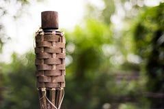 Nahaufnahme des traditionellen Bambusses setzt Öllampe auf Naturhintergrund in Brand lizenzfreie stockfotos