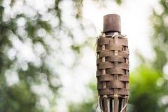 Nahaufnahme des traditionellen Bambusses setzt Öllampe auf Naturhintergrund in Brand lizenzfreie stockbilder