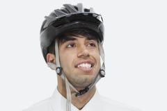 Nahaufnahme des tragenden Radfahrensturzhelms des indischen Geschäftsmannes beim Schauen weg gegen grauen Hintergrund Lizenzfreies Stockfoto