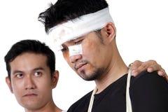 Nahaufnahme des traurigen verletzten Mannes mit seinem mitfühlenden Freund Lizenzfreie Stockbilder