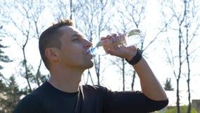 Nahaufnahme des Trinkwassers des jungen durstigen Athleten von der Flasche nach Training stock video footage