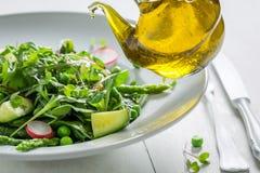 Nahaufnahme des vegetarischen Salats mit Mischung des Gemüses und des Öls lizenzfreies stockfoto