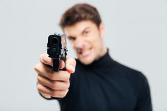Nahaufnahme des verärgerten jungen Mannes, der mit Gewehr auf Ihnen zeigt lizenzfreie stockfotografie