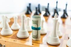 Nahaufnahme des verdrehten Geldes an Bord stehend anstelle Schach piec Stockbild
