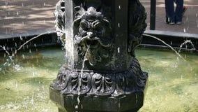 Nahaufnahme des Wasser-Spritzens aus einem Grün und einem eleganten Bronzebrunnen heraus, während eines hellen Sommertages oming stock footage