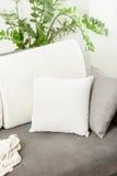 Nahaufnahme des weißen dekorativen Kissens, das auf grauem Sofa am Leben liegt Stockbilder
