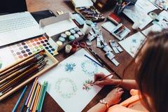Nahaufnahme des weiblichen Designers Blumenzusammensetzungen mit den Zeichenstiften zeichnend, die am Arbeitsplatz umgeben mit Fa Stockfotos