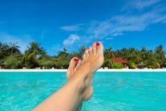 Nahaufnahme des weiblichen Fußes im blauen Wasser auf dem tropischen Strand Stockbild