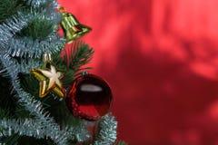Nahaufnahme des Weihnachtsbaums verziert mit Verzierungen im reichen glänzenden roten Hintergrund - mit copyspace Stockfoto