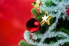 Nahaufnahme des Weihnachtsbaums verziert mit Verzierungen im reichen glänzenden roten Hintergrund - mit copyspace Lizenzfreies Stockbild