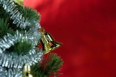 Nahaufnahme des Weihnachtsbaums verziert mit Verzierungen im reichen glänzenden roten Hintergrund - mit copyspace Stockfotografie