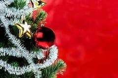 Nahaufnahme des Weihnachtsbaums verziert mit Verzierungen im reichen glänzenden roten Hintergrund - mit copyspace Stockfotos