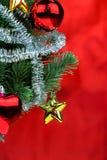 Nahaufnahme des Weihnachtsbaums verziert mit Verzierungen im reichen glänzenden roten Hintergrund - Porträtansicht Stockbilder
