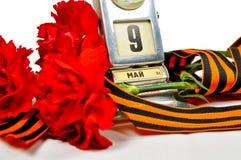 Nahaufnahme des Weinlesemetalltischkalenders mit am 9. Mai Datum und George-Band und rote Gartennelken Stockfotografie