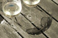 Nahaufnahme des Weins u. der Sonnenbrillen auf Patiotabelle - Tonne Stockfotografie