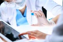 Nahaufnahme des wissenschaftlichen Forschungsteams mit klarer Lösung im Labor Blonder weiblicher Chemiker hält Reagenzglas des Gl Stockbild