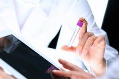 Nahaufnahme des wissenschaftlichen Forschungsteams mit klarer Lösung im Labor Blonder weiblicher Chemiker hält Reagenzglas des Gl Stockfotos