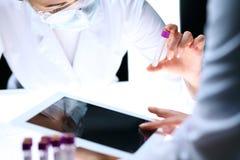 Nahaufnahme des wissenschaftlichen Forschungsteams mit klarer Lösung im Labor Blonder weiblicher Chemiker hält Reagenzglas des Gl Stockfoto
