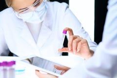 Nahaufnahme des wissenschaftlichen Forschungsteams mit klarer Lösung im Labor Blonder weiblicher Chemiker hält Reagenzglas des Gl Stockfotografie