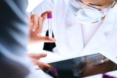 Nahaufnahme des wissenschaftlichen Forschungsteams mit klarer Lösung im Labor Blonder weiblicher Chemiker hält Reagenzglas des Gl Stockbilder
