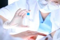 Nahaufnahme des wissenschaftlichen Forschungsteams mit klarer Lösung im Labor Blonder weiblicher Chemiker hält Reagenzglas des Gl Lizenzfreie Stockfotografie