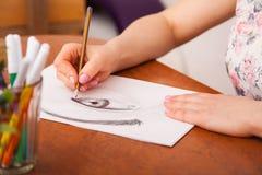 Nahaufnahme des Zeichnens des menschlichen Auges am Schreibtisch Lizenzfreie Stockbilder